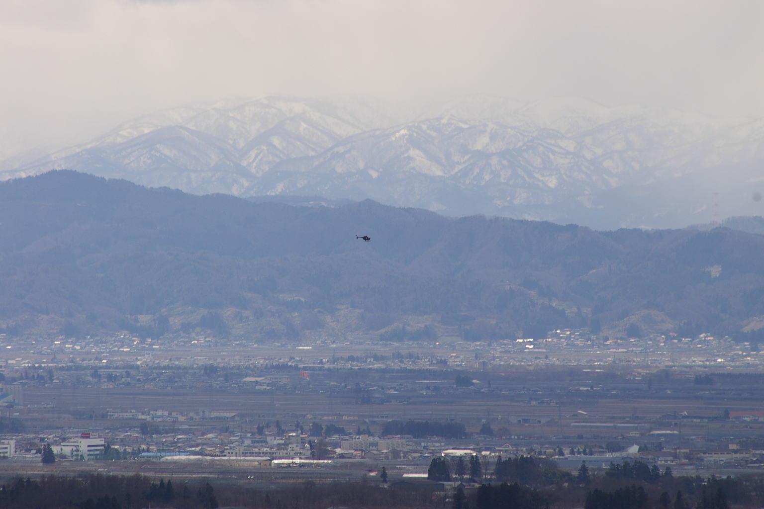 遠くには、朝日連峰を背景に自衛隊のヘリコプターが飛んでいます。