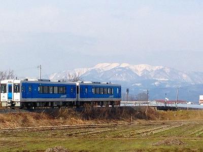 葉山を背景に早春を駆ける電車